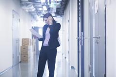 Young woman standing in office corridor looking down at paperwork scratching Stock Photos
