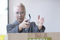 Mature woman behind podium giving lecture holding remote control, gesticulating - stock photo