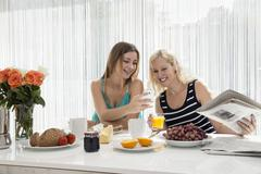 Women sitting at dining table enjoying a continental breakfast together, looking - stock photo