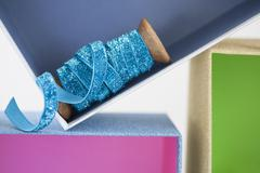 Wooden reel of sparkly blue ribbon in gift box - stock photo