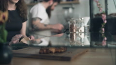 Waitress picking up croissant at the coffee shop - stock footage