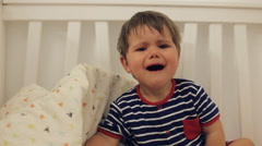 Little cute boy wearing blue striped pijama crying in the bed Stock Footage