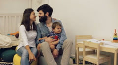 A happy family embracing with a child at home - stock footage