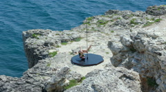 Fit girl wearing bodysuit doing pole dancing fitness exercise on rocky cliff Stock Footage