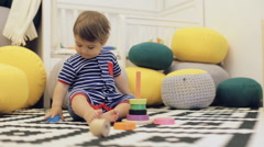 Cute kid in blue bodysuit playing colorful tower at floor Stock Footage