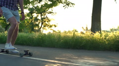 close up male legs on moving longboard in sun light slow motion - stock footage