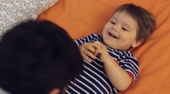 Beautiful young mother, father and son lying and playing together on a bed Stock Footage