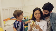 Happy parents feeding toddler boy healthy food at home, cute baby eating banana - stock footage