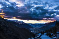 Distant view over snow covered rooftops at dusk, Valtellina, Italy Stock Photos