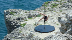Strong girl poledancer performing pole dance tricks and spins on rocky cliff Stock Footage