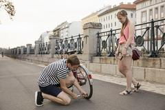 Young woman watching young man kneeling inflating bicycle tyre - stock photo