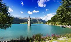 Church spire in turquoise lake, Trentino Alto Adige, Italy - stock photo