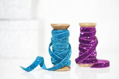 Wooden reels of sparkly blue and purple ribbon Stock Photos