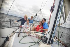 Family relaxing on sailboat, looking away smiling - stock photo