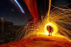 Mature man creating long exposure light painting on cliff side, Moab, Utah, USA Stock Photos