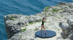 Slow motion of strong girl performing fitness pole dance on rocky cliff by sea Stock Footage