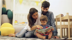 Young parents mom and dad reading children book to baby son on the floor at home Stock Footage