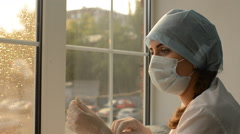 Woman doctor in medical mask puts on rubber gloves on the background of the Stock Footage