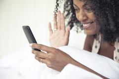 Woman waving at smartphone while doing video chat Kuvituskuvat