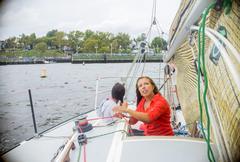 Young woman adjusting sail on sailboat, looking up - stock photo