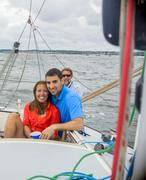 Couple relaxing on sailboat, looking at camera smiling - stock photo