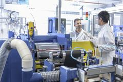 Scientists with lithium ion battery production line in battery research facility - stock photo