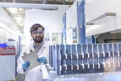 Scientist with lithium ion pouch cell manufacture machine in battery research Stock Photos