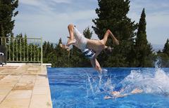 Three boys diving into apartment swimming pool Stock Photos
