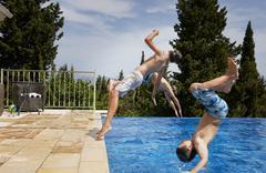 Three boys diving backward into apartment swimming pool - stock photo