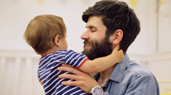 Handsome smiling bearded man lifting up his son in blue striped bodysuit Stock Footage