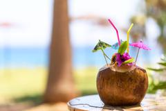 Coconut with drinking straw, umbrellas and flowers, near a palm tree Stock Photos