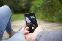 Heterosexual couple sitting outdoors, using smartphone, low section - stock photo