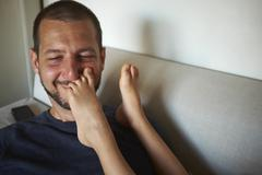 Father sitting on sofa, son's bare feet touching his face Stock Photos