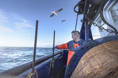 Fisherman looking out to sea on trawler Stock Photos
