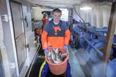Fisherman with basket of fish on trawler, portrait - stock photo