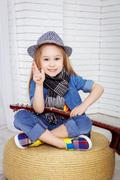 little girl sitting in the lotus position and holding a guitar - stock photo