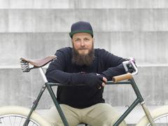 Urban cyclist on steps leaning on bicycle Stock Photos