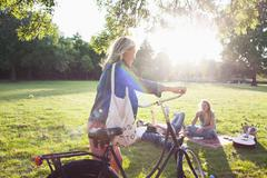 Young woman arriving on bicycle to sunset park party - stock photo