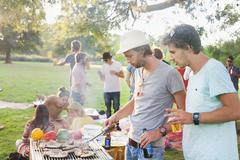 Young men barbecuing at group party in park Stock Photos