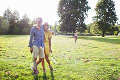 Romantic young couple with badminton rackets  in sunlit park - stock photo