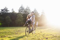 Young woman on handlebars of boyfriends bicycle at party in park - stock photo