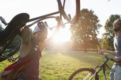 Two male friends arriving in park with bicycles at sunset - stock photo