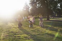 Crowds of adult friends arriving on bicycles to sunset park party Stock Photos