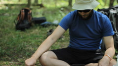 The man controls the gas burner in the forest. He is sitting on the ground and Stock Footage