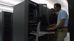 Reveling view of two men working on network server Stock Footage