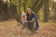 Mid adult woman and baby daughter petting dog in autumn park Stock Photos