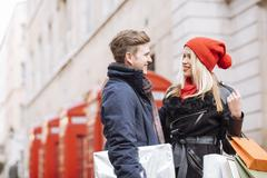 Young shopping couple and red phone boxes, London, UK Stock Photos