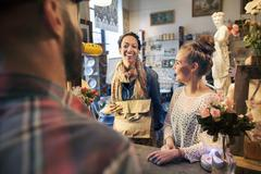 Two happy young female customers buying from vintage shop - stock photo