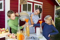 Teenage boy and siblings pouring fresh orange juice to sell at roadside - stock photo