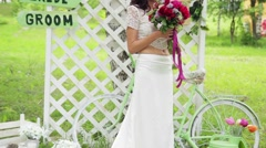 The bride in a white dress and red bouquet in the decoration - stock footage
